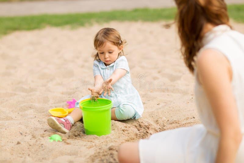 De spelen van weinig babymeisje met speelgoed in zandbak stock foto's