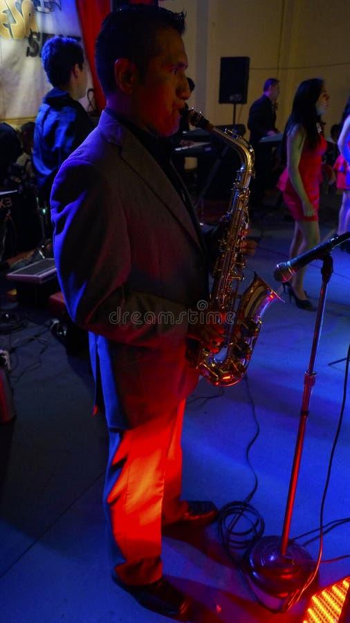 De spelensaxofoon van de muziekmens in een band stock afbeelding