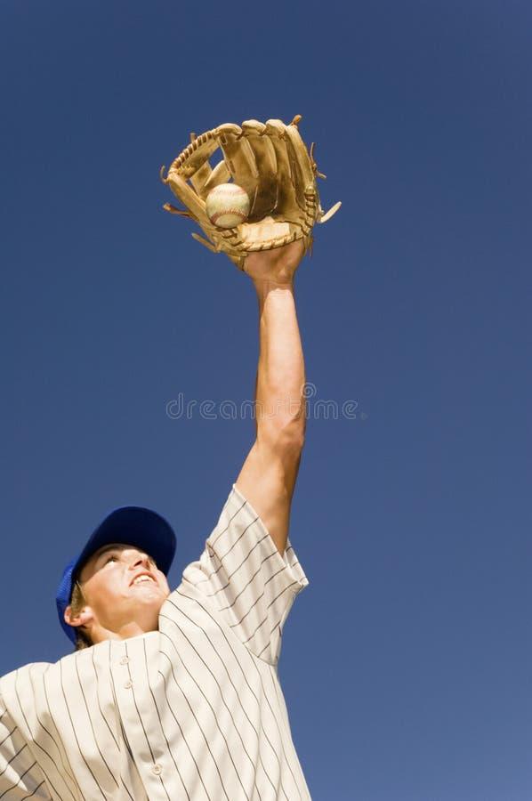 De Speler die van het honkbal de Bal van de Basis proberen te vangen stock foto's