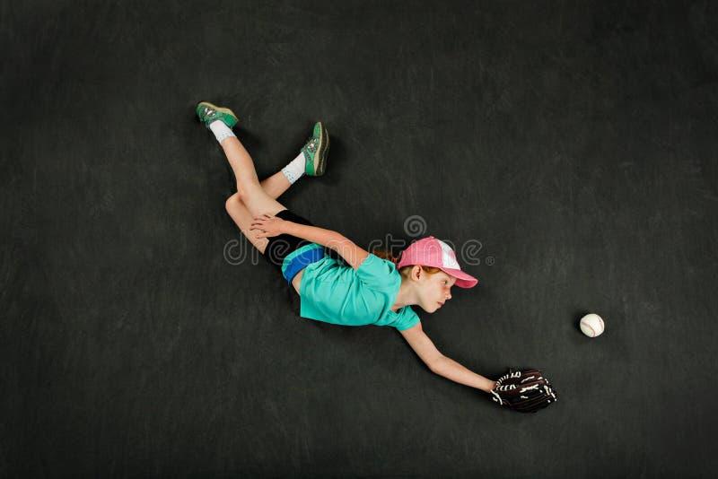 De speler die van het meisjeshonkbal een het duiken vangst maken stock afbeeldingen