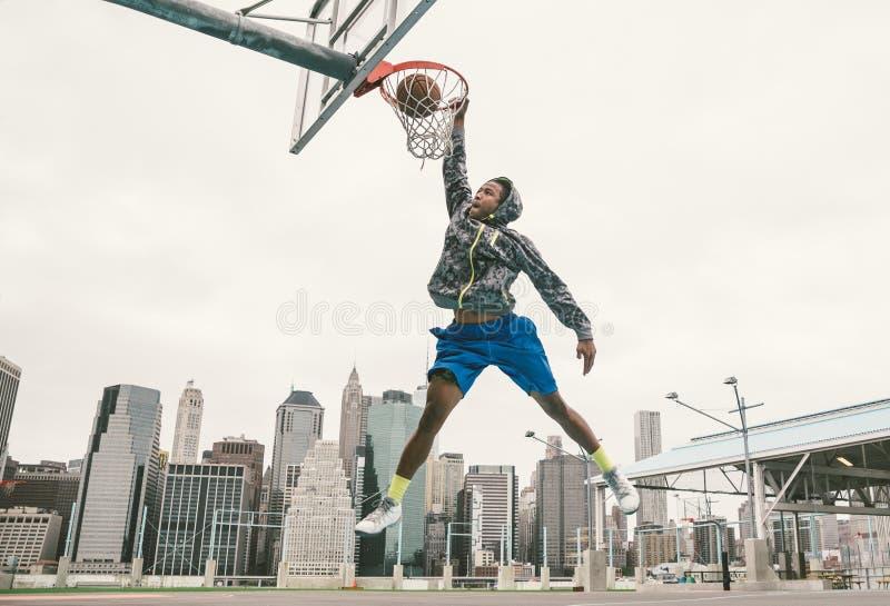 De speler die van het straatbasketbal machtskrottenwijk uitvoeren dompelt onder stock foto