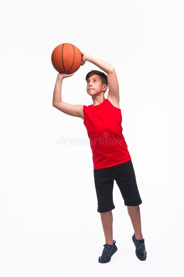De speler die van het tienerbasketbal een bal werpen royalty-vrije stock foto's