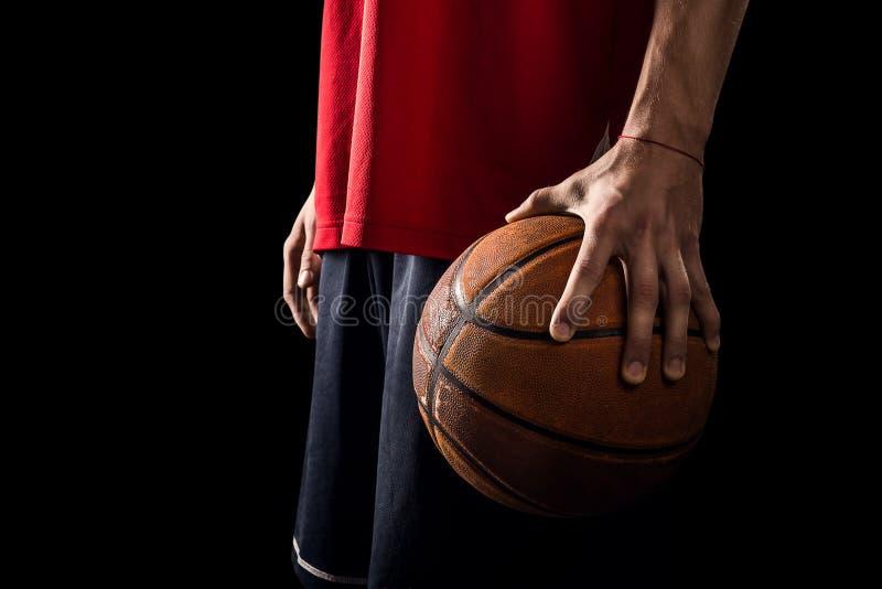 De speler houdt een Basketbalbal in één hand royalty-vrije stock foto's