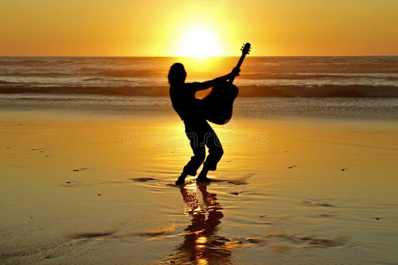 De speler van de gitaar op het strand royalty-vrije stock afbeelding