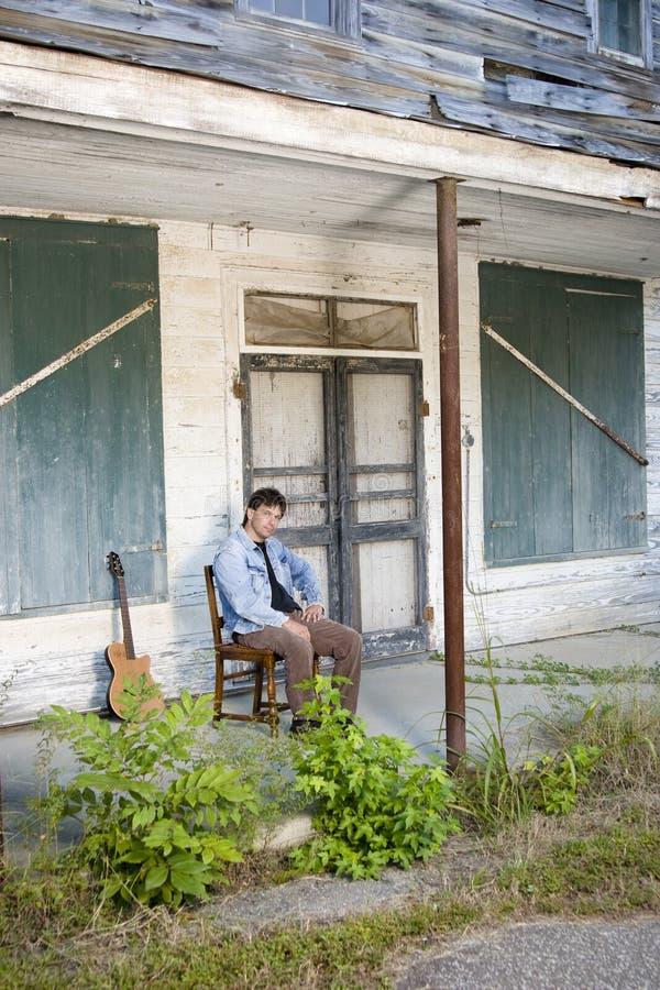 De speler van de gitaar op oude portiek stock foto