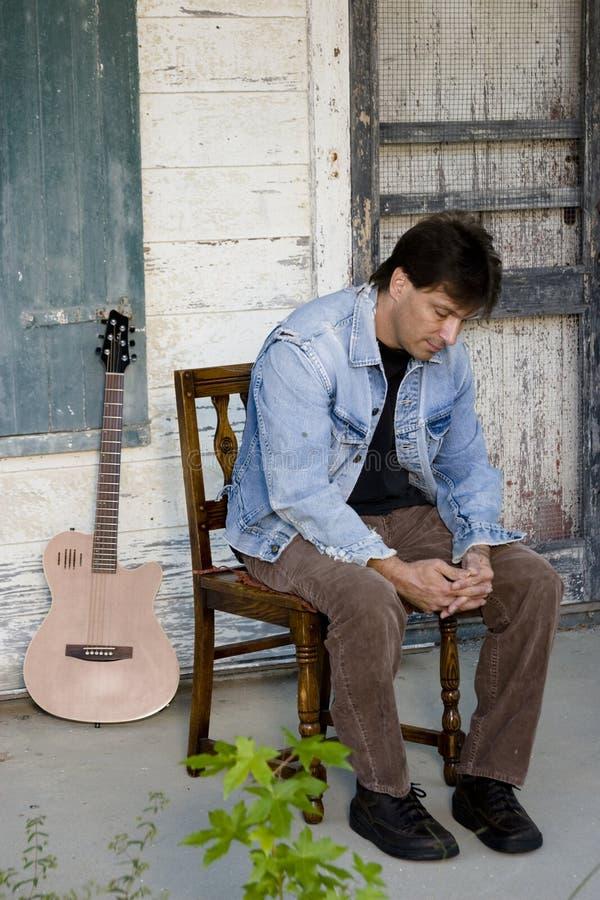 De speler van de gitaar op portiek stock foto