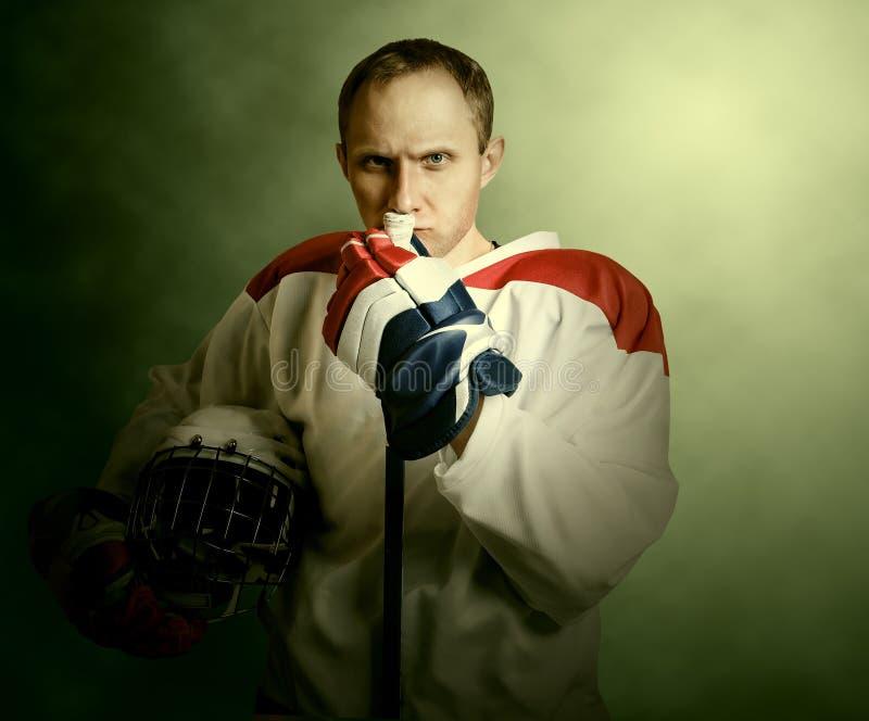 De speler van het portretijshockey op dramatickachtergrond royalty-vrije stock afbeeldingen