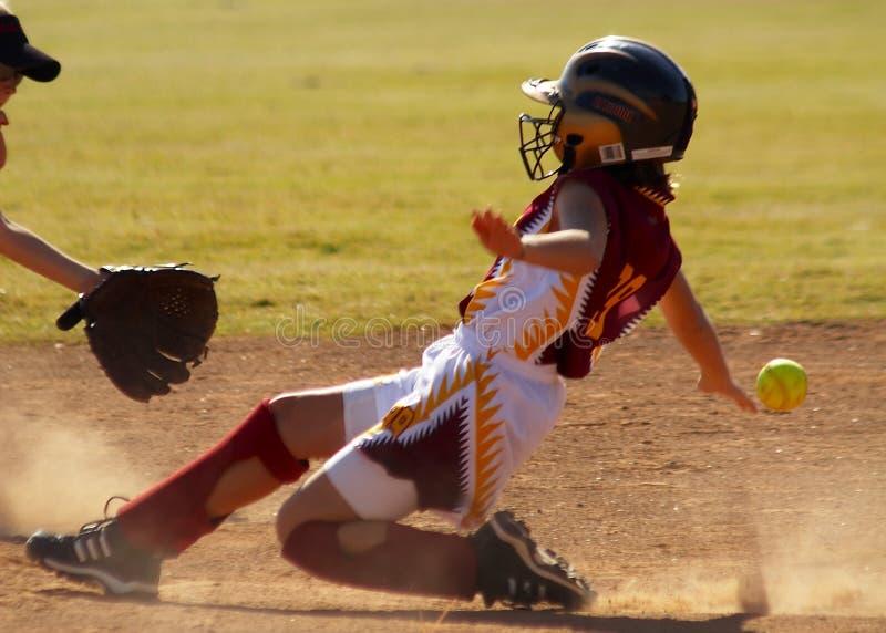De speler van het softball het glijden stock foto's