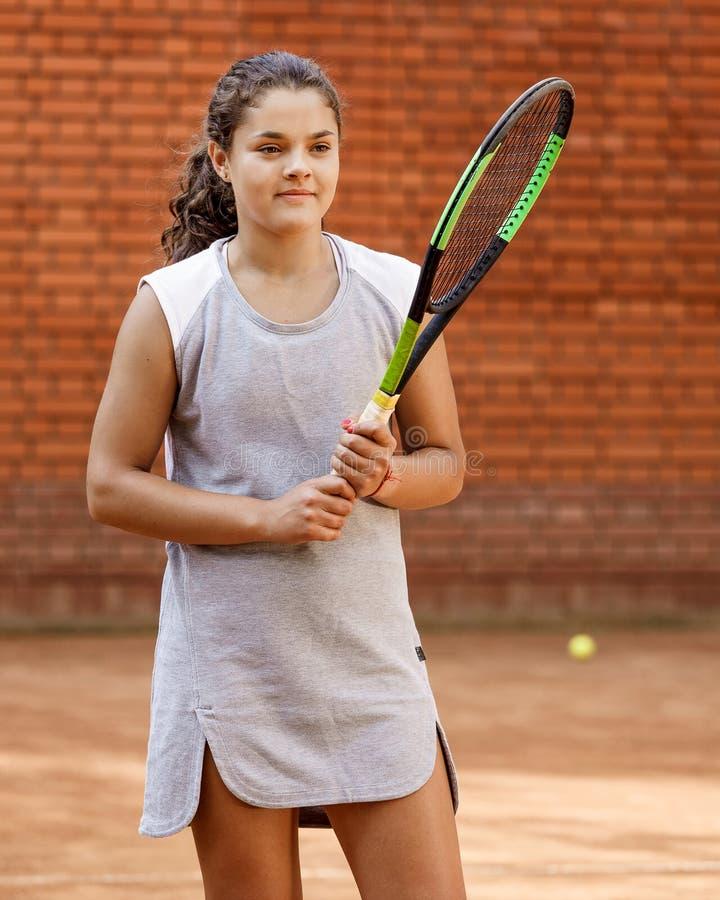 De spelermeisje van het tienertennis van de het meisjesracket van het opleidingshof van het de bal leert het donkerbruine lange h stock afbeelding