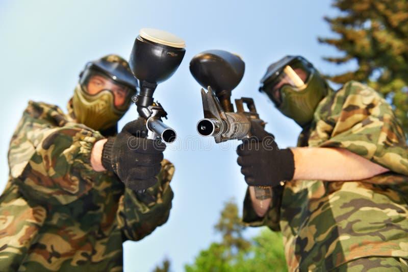 De spelers van Paintball met kanonnen stock afbeelding