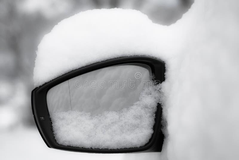 De spiegel dichte omhooggaand van de autovleugel, snowcapped in zwart-wit stock foto's