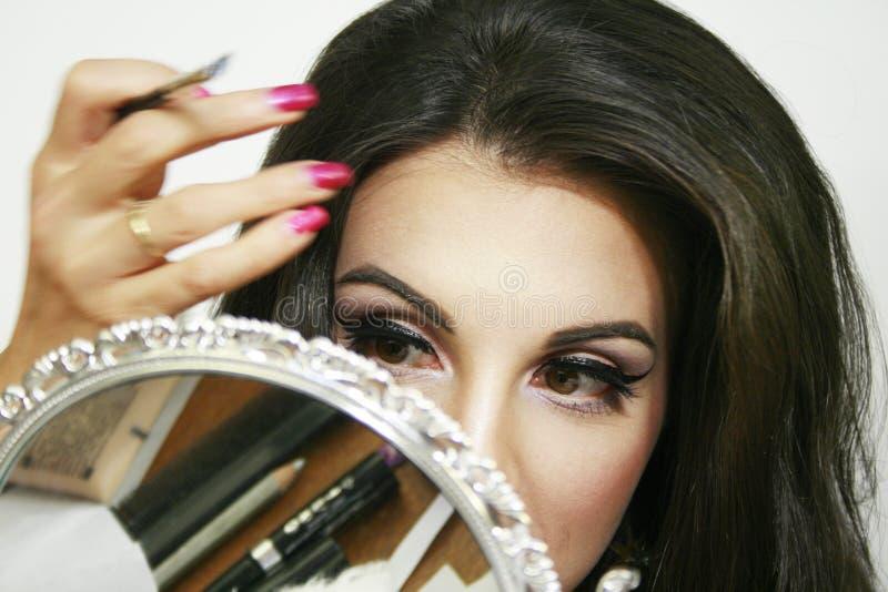 De spiegel wijst op schoonheidsmiddel en het make-upmateriaal, mooi meisje doet haar make-up, handbeweging, roze oogschaduw en aa royalty-vrije stock afbeeldingen