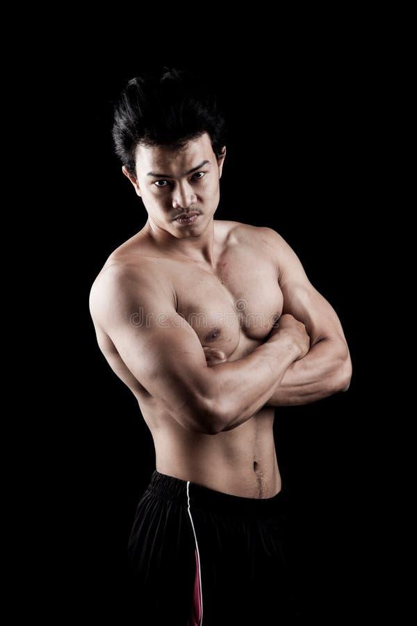 De spier Aziatische mens toont zijn lichaam royalty-vrije stock foto's