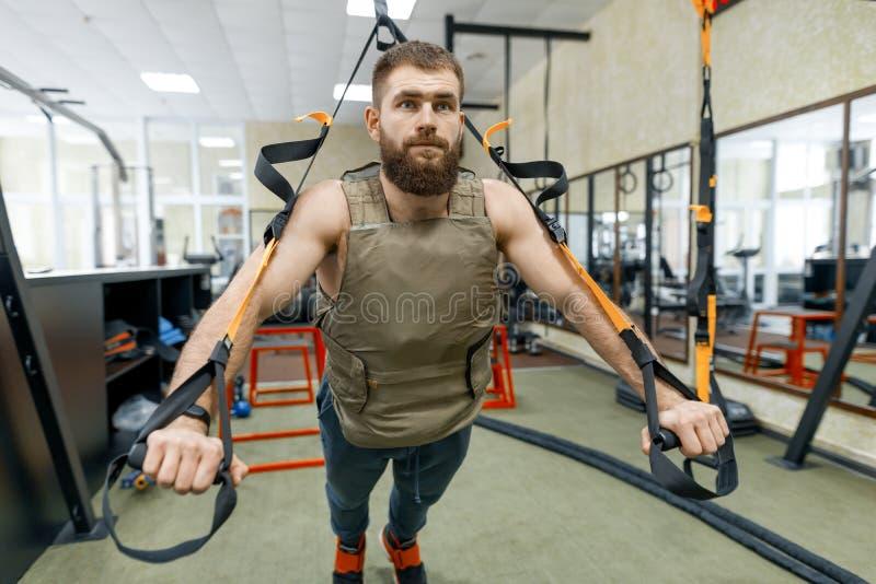 De spier gebaarde mens kleedde zich in militair gewogen gepantserd vest die oefeningen doen gebruikend riemensystemen in de gymna royalty-vrije stock afbeeldingen