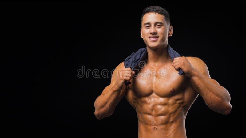 De spier jonge mens in studio op donkere achtergrond toont de verschillende bewegingen en de lichaamsdelen stock afbeeldingen
