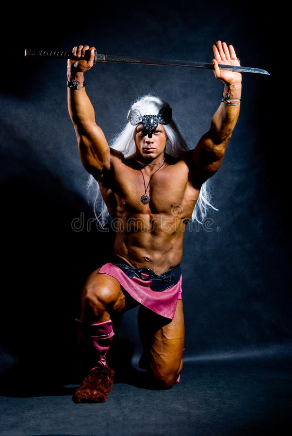 De spier mens in een beeld van een barbaarse strijder met zwaard heft op stock foto's