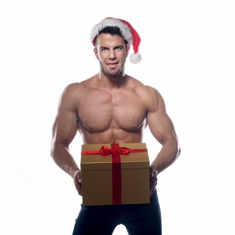 De spier, sexy Kerstman met gift stock afbeeldingen
