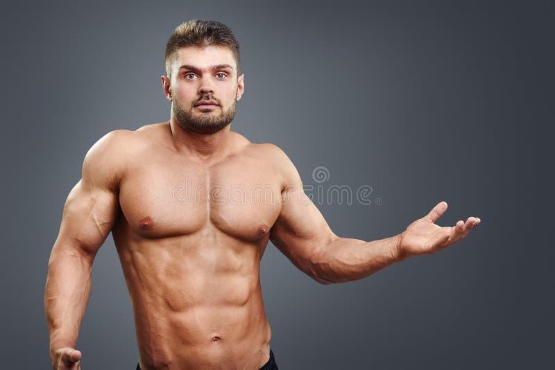 De spier shirtless jonge mens verwarde en haalt op royalty-vrije stock foto