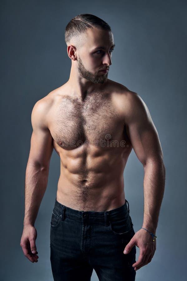 De spier shirtless mens die bevinden zich met dient zakken in stock afbeelding