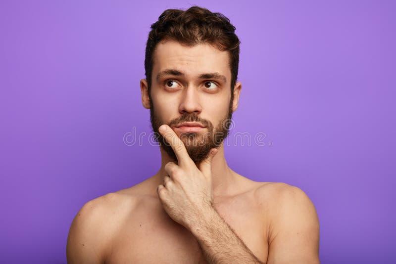 De spier shirtless mens is onzeker, houdend kin met vinger royalty-vrije stock afbeelding