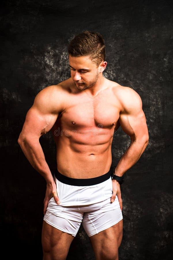 De spieren van de bodybuilderverbuiging tegen donkere achtergrond stock afbeeldingen