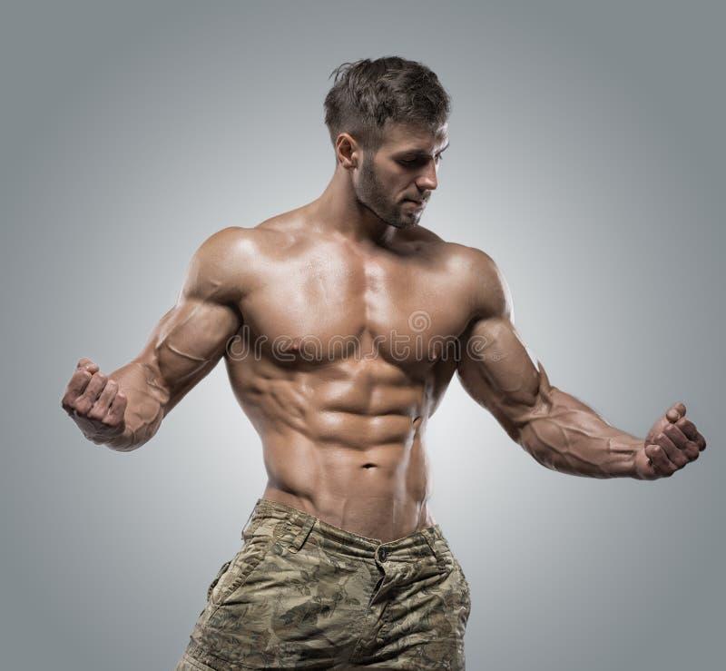 De spiermens van de atletenbodybuilder op een grijze achtergrond royalty-vrije stock afbeeldingen