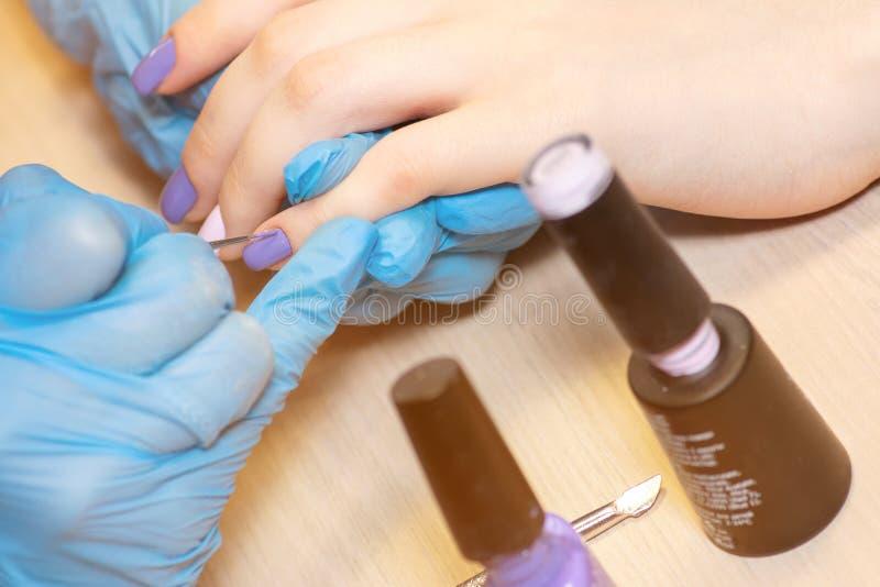 De spijkers van de close-up gezonde natuurlijke vrouw in schoonheidssalon Manicurehand het schilderen cliëntspijkers Het behande royalty-vrije stock foto's
