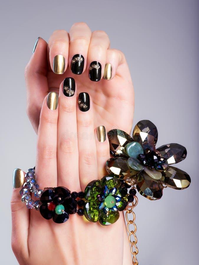 De spijkers van de mooie vrouw met creatieve manicure en juwelen royalty-vrije stock foto's