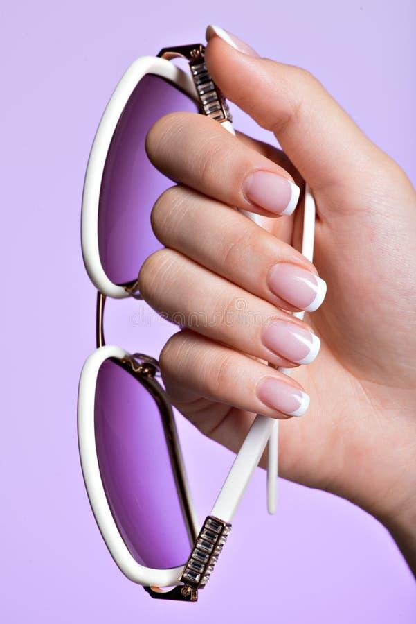 De spijkers van de vrouw met mooie Franse witte manicure stock afbeeldingen