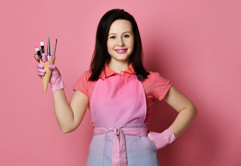 De spijkertechnicus in roze schort en geneeskundehandschoenen houdt een wafelkegel met instrumenten voor spijkerssalon royalty-vrije stock foto