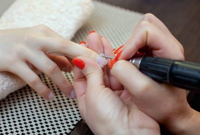 De spijkertechnicus zaagt en maakt een spijkervorm tijdens de procedure van spijkeruitbreidingen met vast gel in de schoonheidssa royalty-vrije stock afbeelding
