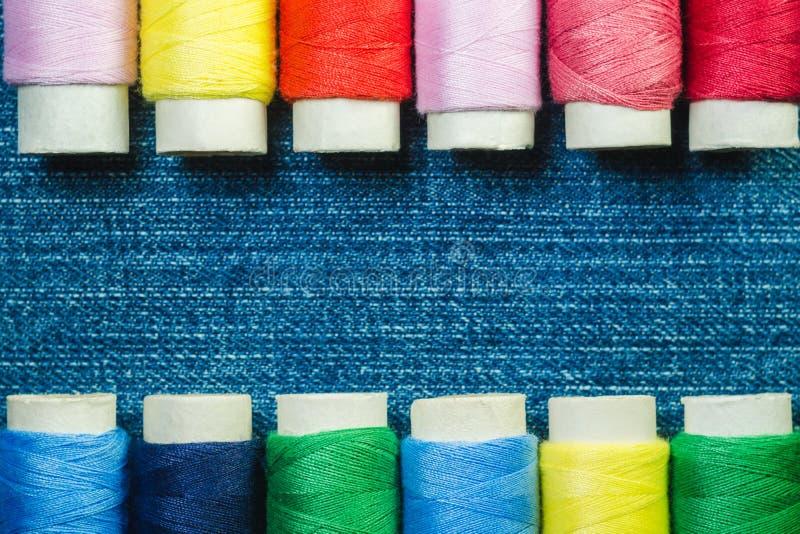 De spoelen van gekleurde naaiende draad schikten in twee rijen op denim met exemplaarruimte royalty-vrije stock foto's