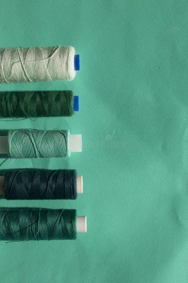 De spoelen van verschillende kleuren worden geschikt op een rij op een turkooise achtergrond In de stijl van vlakte lag stock foto