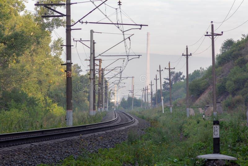 De spoorweg die het de herfstbos aan de fabriekspit doornemen royalty-vrije stock foto's
