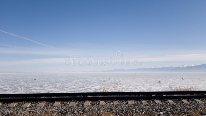 De spoorweg van circum-Baikal van spoorwegsporen op de achtergrond van meer Baikal in de winter Sneeuw en ijs op het meer in Rusl stock foto