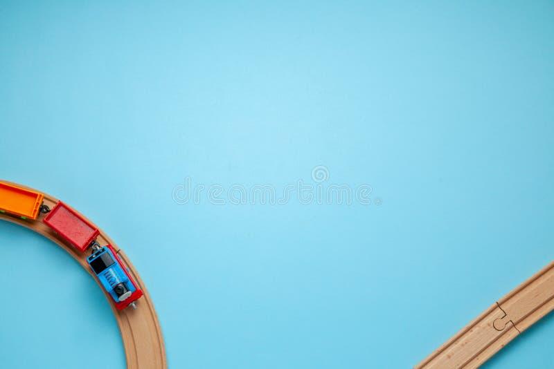 De spoorweg van kinderen met houten sporen op een blauwe achtergrond, hoogste mening Exemplaarruimte voor tekst stock fotografie