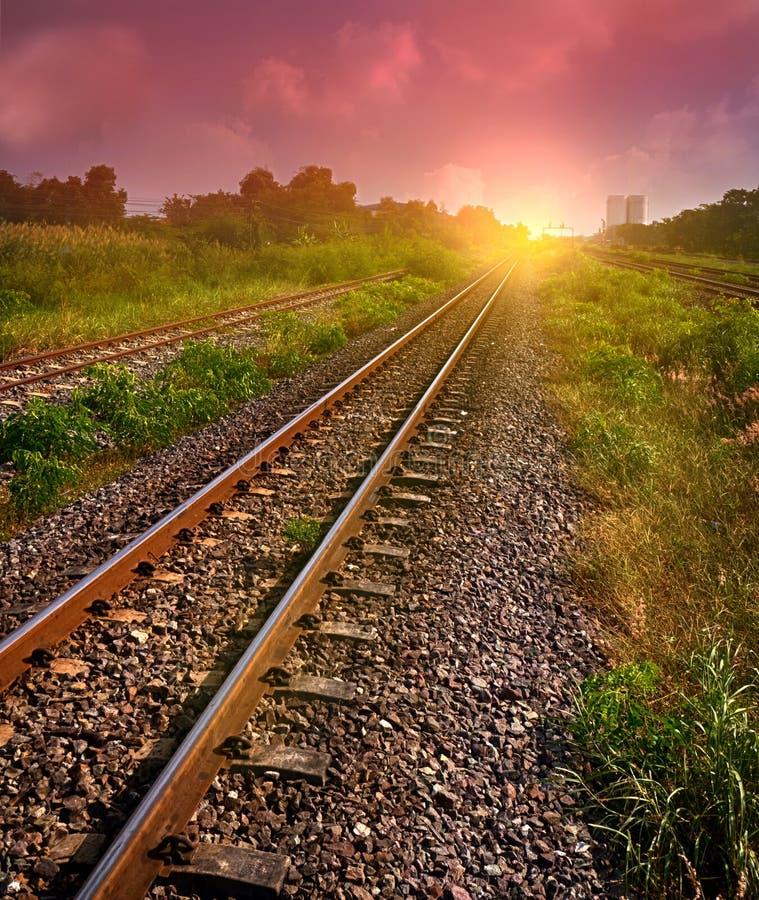 De spoorwegsporen in zon heffen ogenblik met gloed van zon op stock fotografie