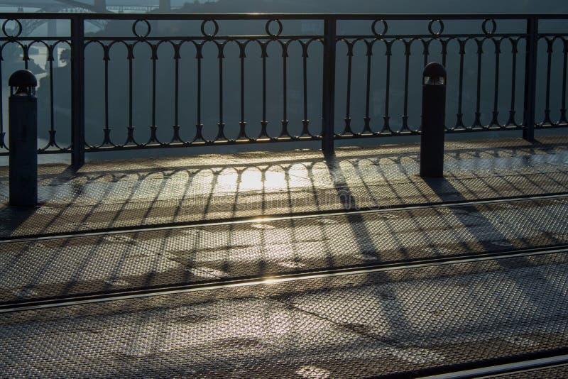 De sporen en het ijzer perken ochtendlicht in Moderne stedelijke architectuur Schaduw van metaalomheining vroeg in de ochtend op  stock fotografie