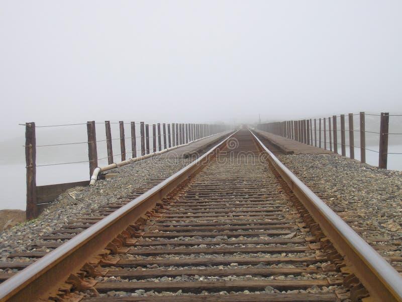 De sporen van de spoorweg in mist stock afbeelding