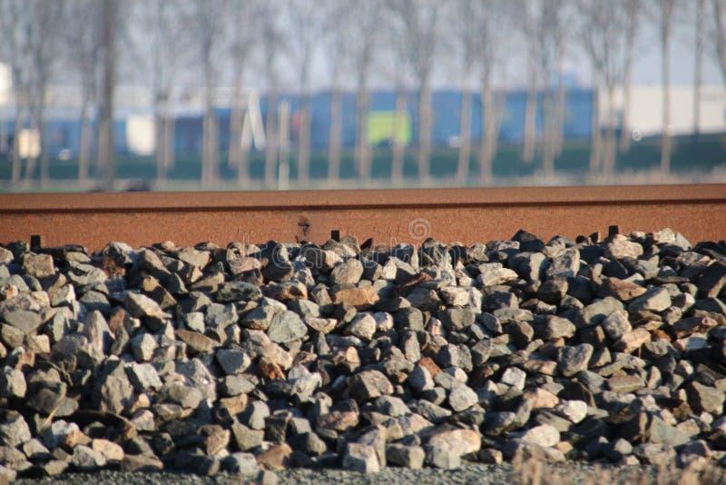 De sporen van trein volgen in roestige kleuren met steen voorbij het bij Gouda in Nederland stock foto's