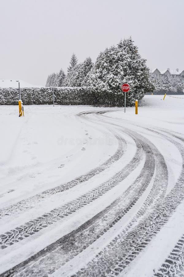 De sporen van de winterbanden op sneeuwwegdraai met eindeteken vooraan stock foto's