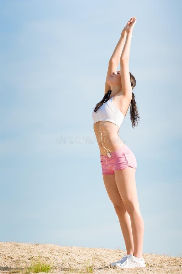 De sport het geschikte vrouw van de zomer uitrekken zich op strand stock afbeelding