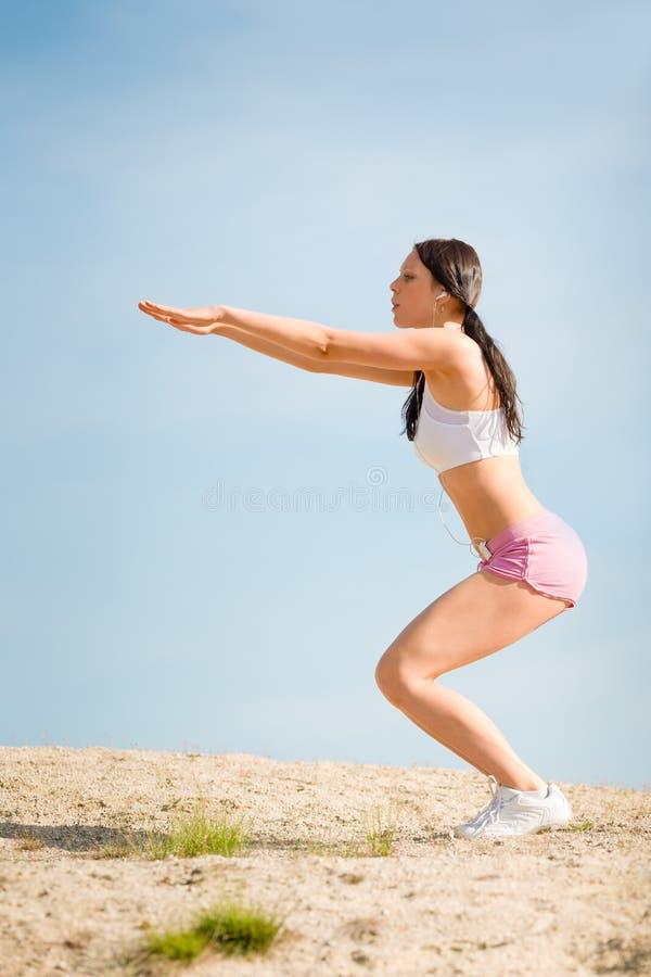 De sport het geschikte vrouw van de zomer uitrekken zich op strand stock afbeeldingen