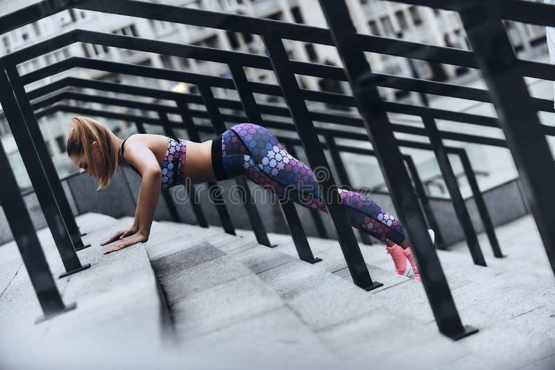 De sport is de manier van haar leven Moderne jonge vrouw in sportkleding die plankpositie houden terwijl in openlucht het uitoefe stock afbeeldingen
