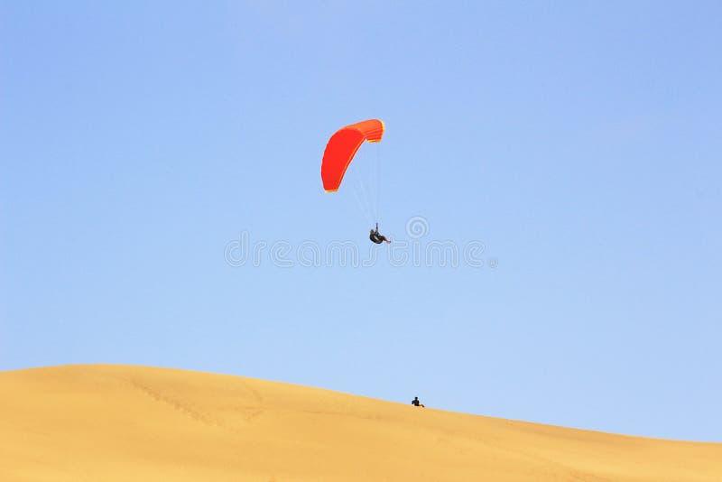 De sport van het springen van het zandduin en het uitvoeren van acrobatische manoeuvres in de lucht tijdens vrije daling alvorens stock foto's