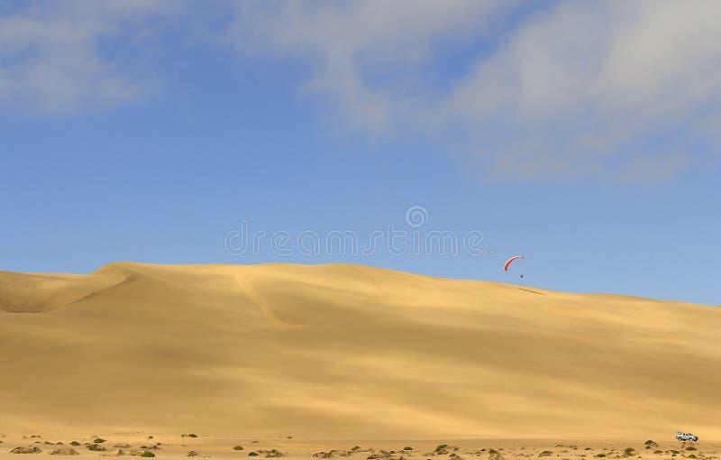De sport van het springen van het zandduin en het uitvoeren van acrobatische manoeuvres in de lucht tijdens vrije daling alvorens stock foto