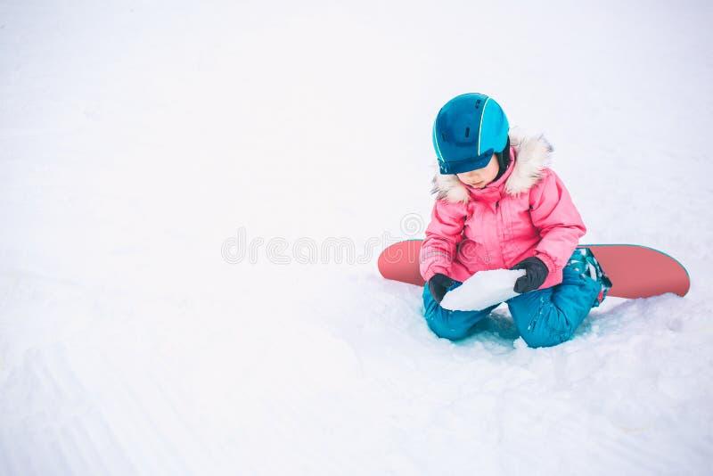 De Sport van de Snowboardwinter Weinig jong geitjemeisje die met sneeuw spelen die warme de winterkleren dragen De achtergrond va royalty-vrije stock fotografie