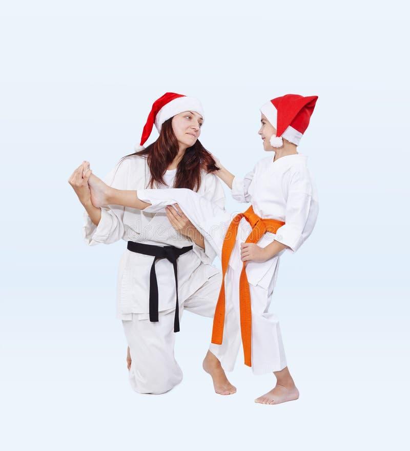 De sportenfamilie in kappen van Santa Claus leidt schopbeen op royalty-vrije stock afbeelding