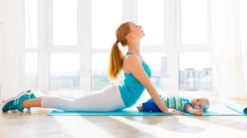 De sportenmoeder is thuis bezig geweest met fitness en yoga met baby stock foto's