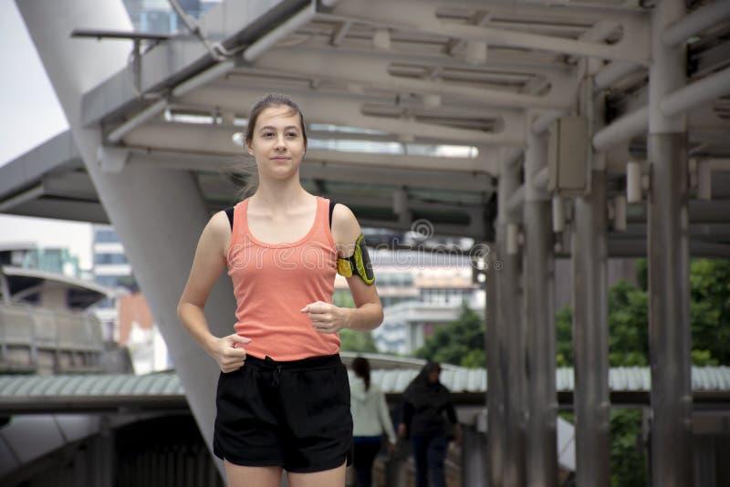 De sportieve jogging van de meisjesagent in openlucht door stadsstraten/gezonde levensstijl royalty-vrije stock afbeelding